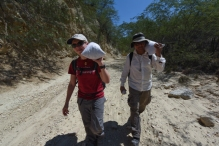 Erin and Félix carry off heavy bags of samples for analysis.